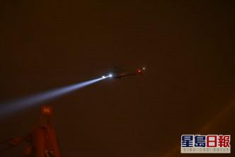 直升机开照明灯协助。